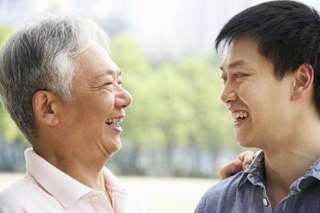 niños platicando: Retrato del padre con el hijo adulto chino en el Parque Foto de archivo