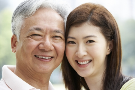 grown ups: Portrait Of Chinese Father With Adult Daughter In Park Stock Photo
