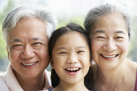 Head And Shoulders Portrait Of Chinese Grandparents With Granddaughter Ride photo