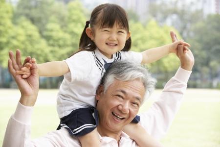 abuelitos: Abuelo chino Dar Ride Nieta En Hombros En El Parque Foto de archivo