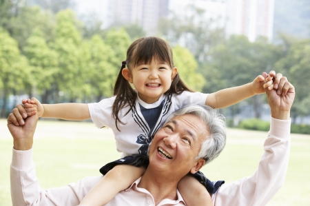 Having Fun: Chinese Grandfather Giving Granddaughter Ride On Shoulders In Park Stock Photo