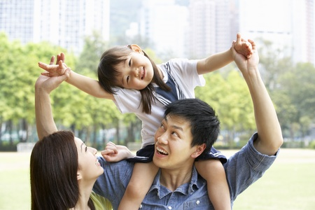 Chinese Family Giving Daughter Ride On Shoulders In Park photo