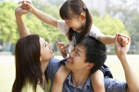 family park: Chinese Family Giving Daughter Ride On Shoulders In Park Stock Photo