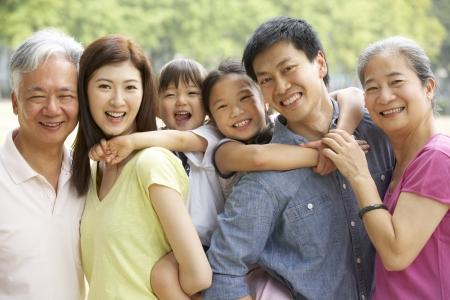 Portrait Of Multi-Generation Chinese Family Relaxing In Park Together photo