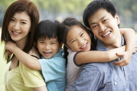 Portrait Of Chinese Family Relaxing In Park Together