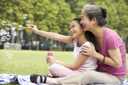 granddaughter: Chinese Grandmother With Granddaughter In Park Blowing Bubbles