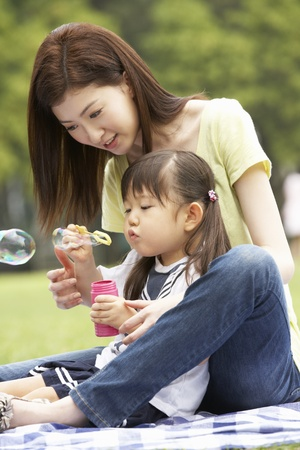 blowing bubbles: Chinese Mother With Daughter In Park Blowing Bubbles Stock Photo