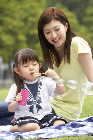 Chinese Mother With Daughter In Park Blowing Bubbles photo