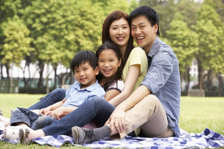 Young Chinese Family Relaxing In Park Together Foto de archivo
