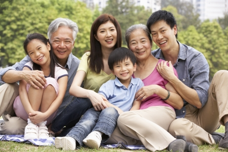 happy asian family: Portrait Of Multi-Generation Chinese Family Relaxing In Park Together
