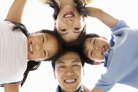 family looking up: Young Chinese Family Looking Down Into Camera Stock Photo