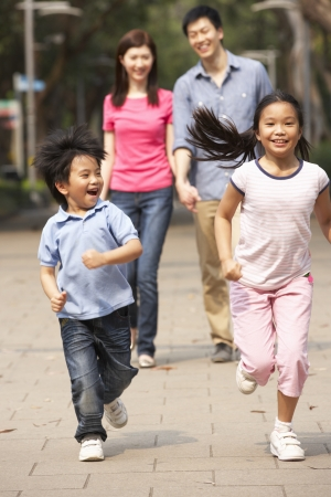 chinese family: Chinese Family Walking Through Park With Running Children