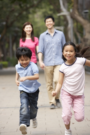 Chinese Family Walking Through Park With Running Children photo