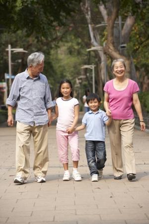 senior asian: Chinese Grandparents Walking Through Park With Grandchildren