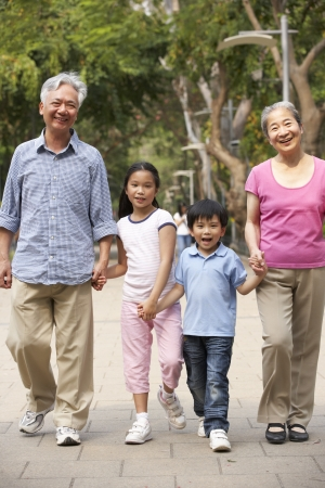 Chinese Grandparents Walking Through Park With Grandchildren photo