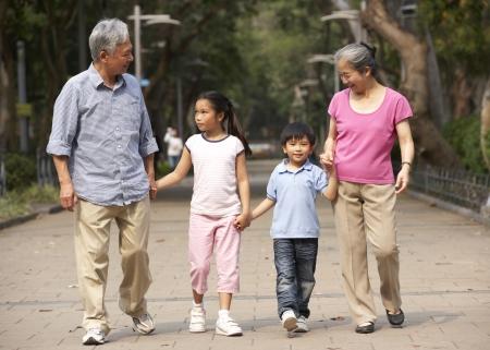 niños caminando: Abuelos chinos a pie a través del parque con los nietos Foto de archivo