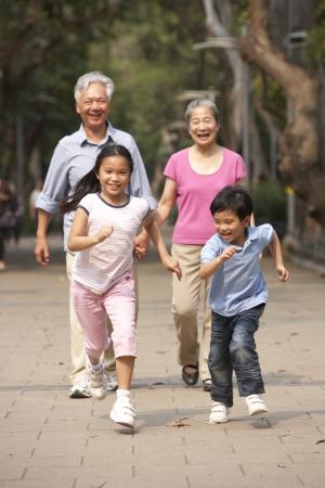 grandchildren: Chinese Grandparents Walking Through Park With Running Grandchildren