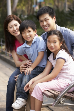 chinese family: Chinese Family Walking Sitting On Bench In Park Together Stock Photo