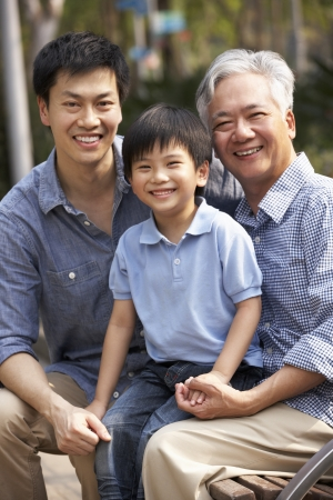 three generation: Male Multi Genenration Chinese Family Group Sitting On Bench In Park Together Stock Photo