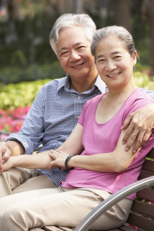 senior asian: Senior Chinese Couple Relaxing On Park Bench Together Stock Photo
