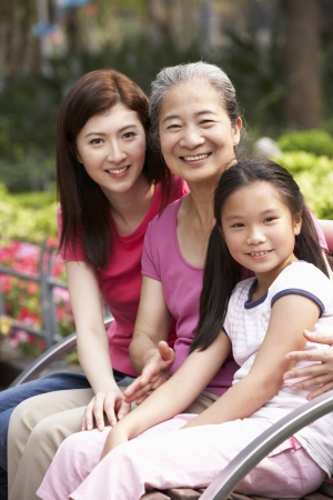 three generations: Female Multi Genenration Chinese Family Group Sitting On Bench In Park Together Stock Photo