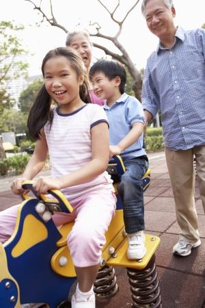 playground ride: Chinese Grandparents Playing With Grandchildren In Playground