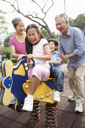 Chinese Grandparents Playing With Grandchildren In Playground photo