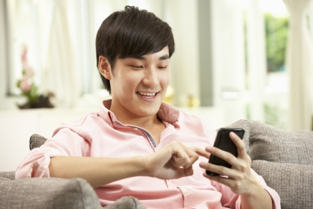 sit up: Young Chinese Man Using Mobile Phone On Sofa At Home