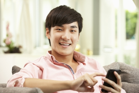 Young Chinese Man Using Mobile Phone On Sofa At Home photo