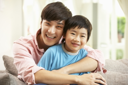 chinese adult: Chinese Father And Son Relaxing On Sofa At Home