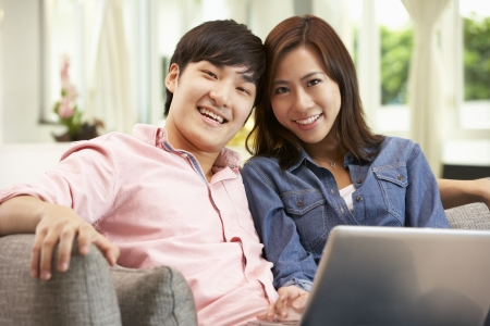 Young Chinese Couple Using Laptop Whilst Relaxing On Sofa At Home photo