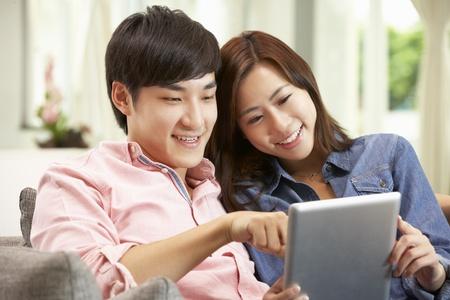 work together: Jonge Chinese koppel die Digitale Tablet, terwijl u ontspannen op de bank thuis
