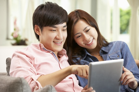 Young Chinese Couple Using Digital Tablet Whilst Relaxing On Sofa At Home photo