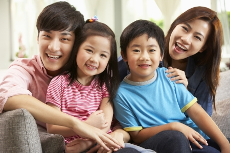 family on couch: Chinese Family Relaxing On Sofa At Home Stock Photo
