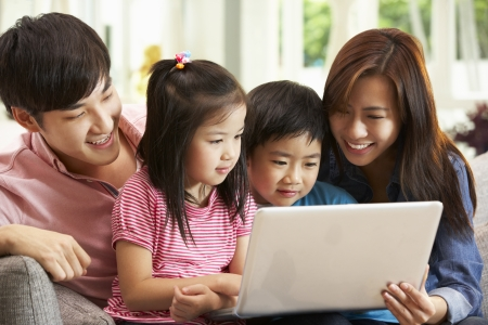 chinese family: Chinese Family Using Laptop Whilst Relaxing On Sofa At Home Stock Photo