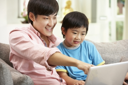 chinese adult: Chinese Father And Son Using Laptop Whilst Relaxing On Sofa At Home