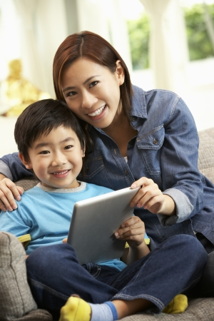 niños chinos: Madre china e hijo que usa la tableta del ordenador mientras está sentado en el sofá en casa