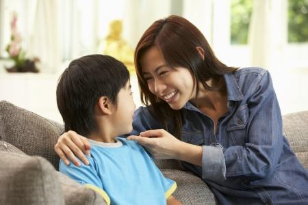 dos personas conversando: Madre china e hijo se sienta en el sof� en casa Juntos