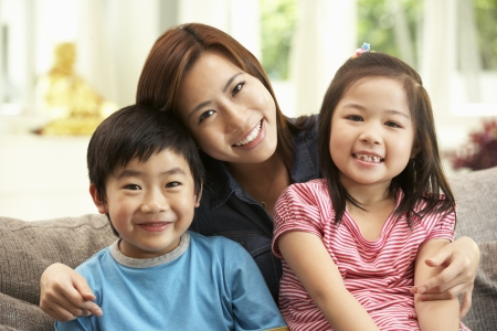 6 7 year old: Chinese Mother And Children Sitting On Sofa At Home Together