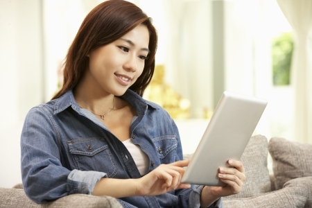 web browsing: Young Chinese Woman Using Digital Tablet Whilst Relaxing On Sofa At Home
