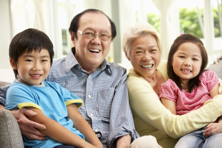 grandmother grandchild: Portrait Of Chinese Grandparents With Grandchildren Relaxing At Home Together Stock Photo