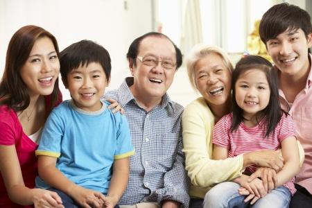 Retrato De Familia multi-generacional chino descansando en su casa, junto Foto de archivo