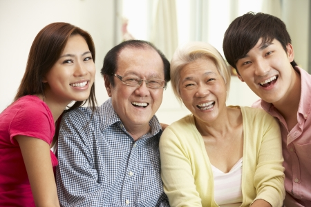 grown ups: Portrait Of Chinese Parents With Adult Children Relaxing At Home Together Stock Photo