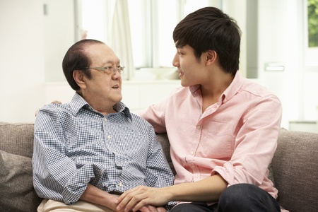 grown ups: Portrait Of Chinese Father With Adult Son Relaxing At Home Stock Photo