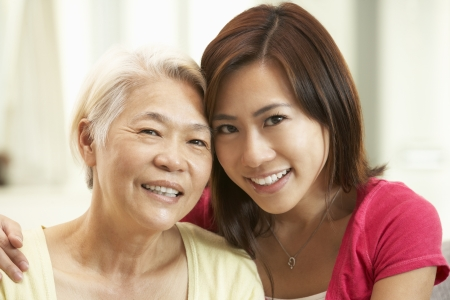 60s adult: Portrait Of Chinese Mother With Adult Daughter Relaxing At Home