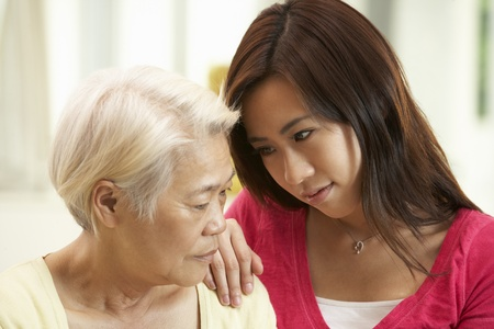 comforted: Unhappy Chinese Mother Being Comforted By Adult Daughter Stock Photo