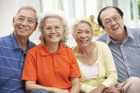 senior group: Group Of Senior Chinese Friends Relaxing On Sofa At Home Stock Photo