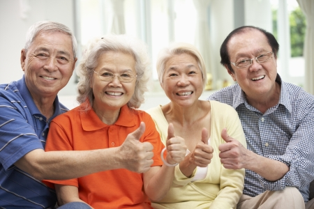 thumbs up group: Group Of Senior Chinese Friends Relaxing On Sofa At Home Stock Photo