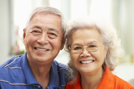 retired couple: Senior Chinese Couple Relaxing On Sofa At Home Stock Photo