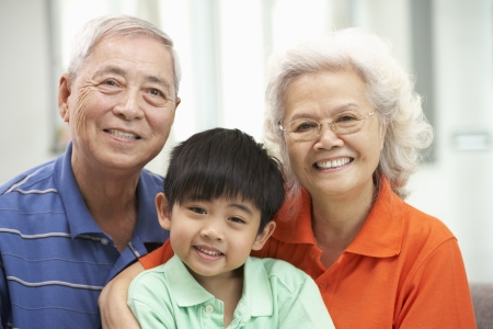 Portrait Of Chinese Grandparents With Grandson Relaxing At Home Together Stock Photo - 18709765